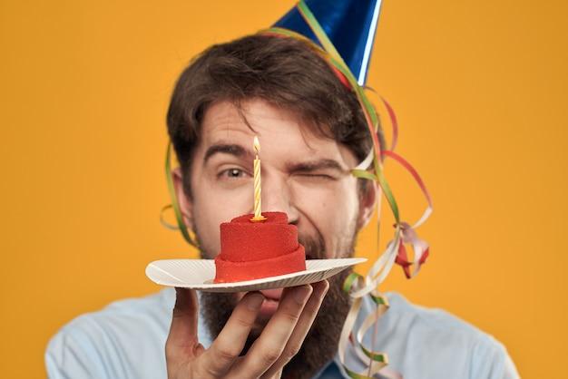 Młody Człowiek Z Uroczystym Tortem Z Plastrami Obchodzi Urodziny W Czapce Premium Zdjęcia