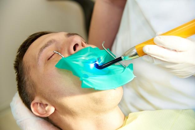Młody Człowiek Z Zamkniętymi Oczami Na Fotelu Dentystycznym. Dentysta Pracuje Z Dentystyczną Lampą Polimeryzacyjną. Premium Zdjęcia
