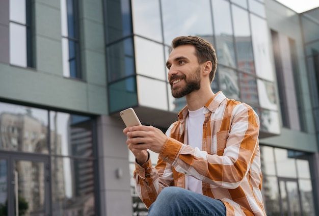 Młody Człowiek Za Pomocą Telefonu Komórkowego, Pracujący W Trybie Online, Siedząc Na Zewnątrz Premium Zdjęcia