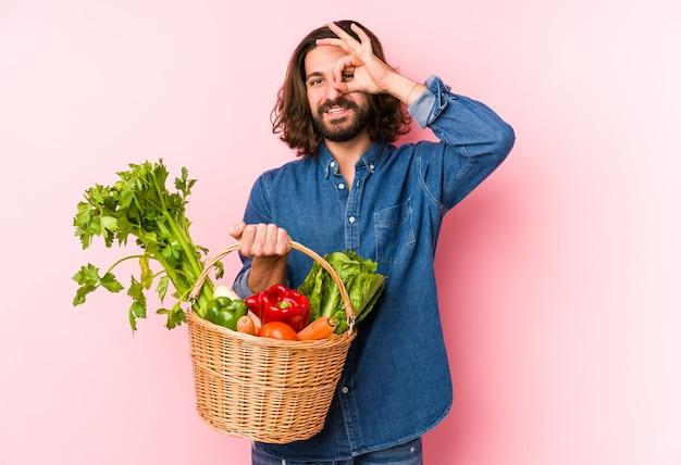 Młody Człowiek Zbierając Organiczne Warzywa Z Ogrodu Na Białym Tle Podekscytowany, Utrzymując Ok Gest Na Oko. Premium Zdjęcia