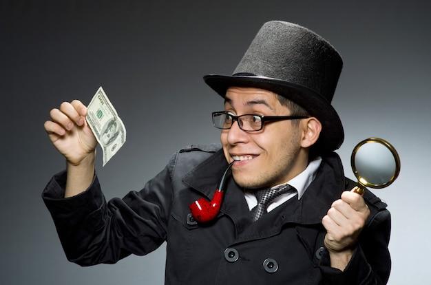 Młody Detektyw W Czarnym Płaszczu Z Pieniędzmi Na Szarym Tle Premium Zdjęcia