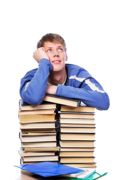 Młody Dorosły Student Prowadził Dziennik Na Stercie Książek, Patrząc W Górę I Myśląc. Darmowe Zdjęcia