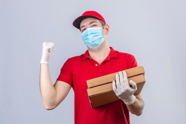 Młody Dostawczyni W Czerwonej Koszulce Polo I Czapce W Masce Medycznej Trzymający Pudełka Po Pizzy Wskazujący Do Tyłu Ręką I Kciukiem Do Góry, Patrząc Pewnie Na Odizolowaną Białą ścianę Darmowe Zdjęcia