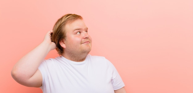 Młody, Duży Mężczyzna Czuje Się Zdziwiony I Zdezorientowany, Drapiąc Się Po Głowie I Patrząc W Bok Na Różową ścianę Premium Zdjęcia
