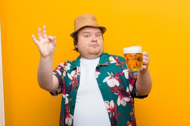 Młody, duży mężczyzna z kuflem piwa na płaskiej ścianie Premium Zdjęcia