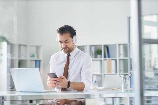Młody Elegancki Mężczyzna W Słuchawkach Przewijania W Smartfonie Przez Miejsce Pracy Przed Laptopem Premium Zdjęcia