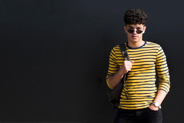 Młody etniczny kędzierzawy mężczyzna w okularach przeciwsłonecznych z plecakiem przeciw czarnemu tłu Darmowe Zdjęcia