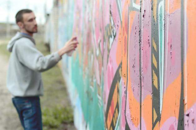 Młody Facet W Szarej Bluzie Z Kapturem Maluje Graffiti W Kolorze Różowym I Zielonym Premium Zdjęcia