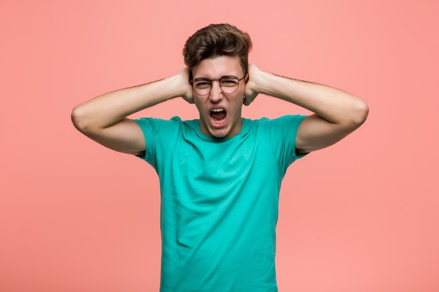 Młody Fajny Kaukaski Mężczyzna Zakrywający Uszy Rękami, Starając Się Nie Słyszeć Zbyt Głośnego Dźwięku Premium Zdjęcia
