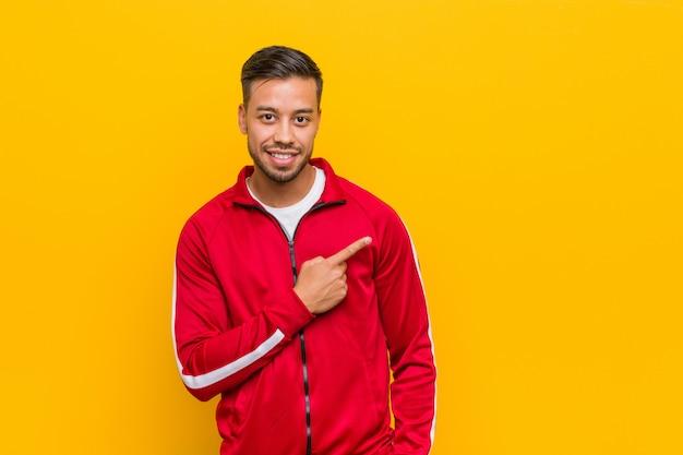 Młody filipiński sprawność fizyczna mężczyzna ono uśmiecha się i wskazuje na boku, pokazuje coś przy pustą przestrzenią. Premium Zdjęcia