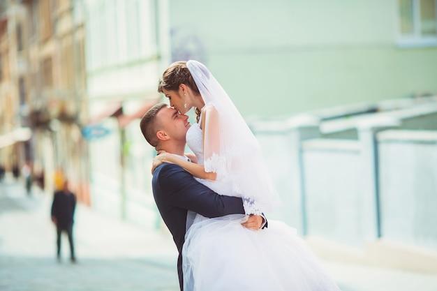 Młody Fornal Trzyma Panny Młodej Na Rękach I Odprowadzeniu Premium Zdjęcia