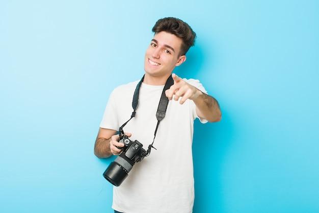 Młody Fotograf Kaukaski Mężczyzna Trzyma Aparat Wesoły Uśmiech Wskazujący Na Przód. Premium Zdjęcia