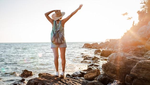 Młody hipster kobieta kapelusz rukzak z rękami do góry, stojąc na szczycie klifu patrząc morze zachód słońca. Premium Zdjęcia