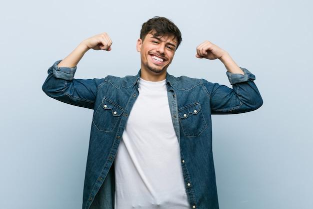 Młody hiszpanin fajny człowiek pokazując gest siły z rękami, symbol kobiecej mocy Premium Zdjęcia
