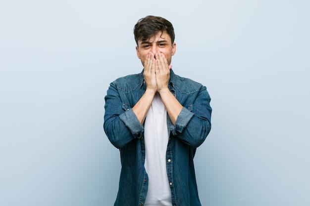 Młody hiszpanin fajny człowiek śmieje się z czegoś, zakrywając usta dłońmi. Premium Zdjęcia