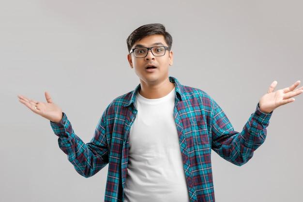 Młody indyjski / azjatycki mężczyzna z zaskoczonym wyrazem twarzy Premium Zdjęcia
