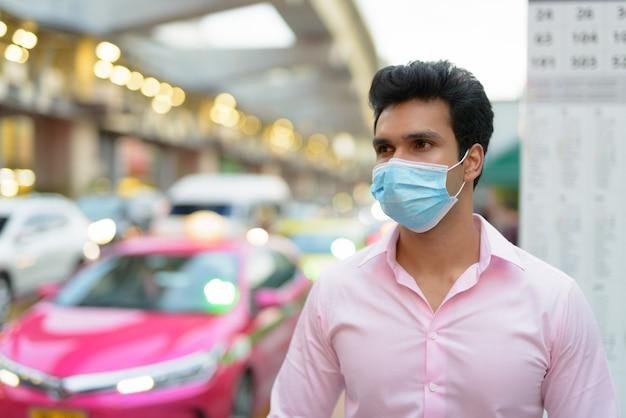 Młody Indyjski Biznesmen Z Maską Czeka Na Przystanku Autobusowym Premium Zdjęcia