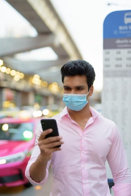 Młody Indyjski Biznesmen Z Maską Za Pomocą Telefonu Na Przystanku Autobusowym Premium Zdjęcia