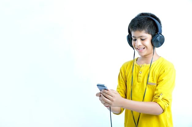 Młody Indyjski ładny Chłopiec Słuchania Muzyki W Słuchawkach Premium Zdjęcia