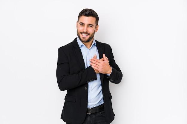 Młody Kaukaski Biznesmen Na Białej ścianie Ma Przyjazny Wyraz, Przyciskając Dłoń Do Klatki Piersiowej. Premium Zdjęcia