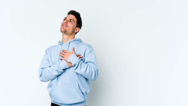 Młody Kaukaski Mężczyzna Na Białej ścianie Ma Przyjazny Wyraz, Przyciskając Dłoń Do Klatki Piersiowej. Koncepcja Miłości. Premium Zdjęcia