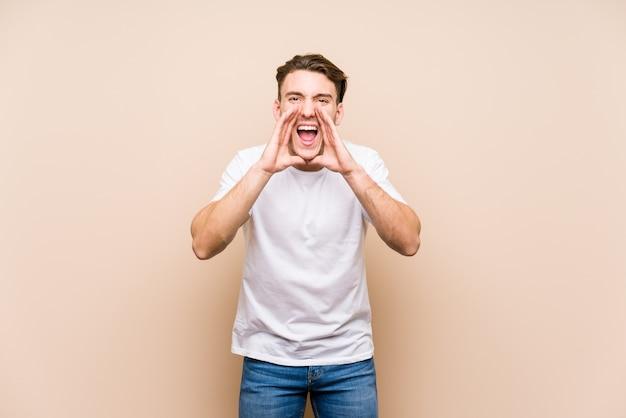 Młody Kaukaski Mężczyzna Pozowanie Na Białym Tle Krzycząc Podekscytowany Do Przodu. Premium Zdjęcia