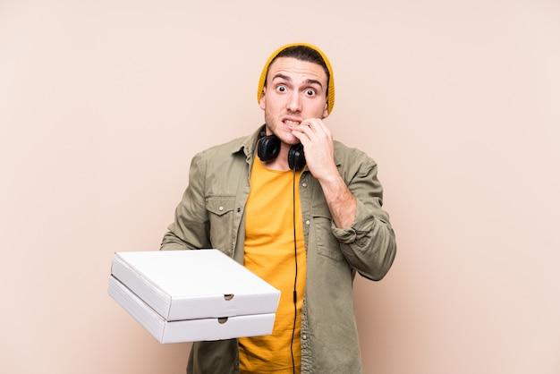 Młody Kaukaski Mężczyzna Trzyma Pizze Gryząc Paznokcie, Nerwowy I Bardzo Niespokojny. Premium Zdjęcia