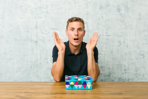 Młody Kaukaski Mężczyzna Trzyma Pudełko Na Stole Zaskoczony I Zszokowany. Premium Zdjęcia