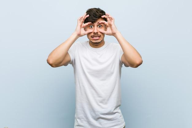 Młody Kaukaski Mężczyzna W Białej Koszulce Z Otwartymi Oczami, Aby Znaleźć Szansę Na Sukces. Premium Zdjęcia