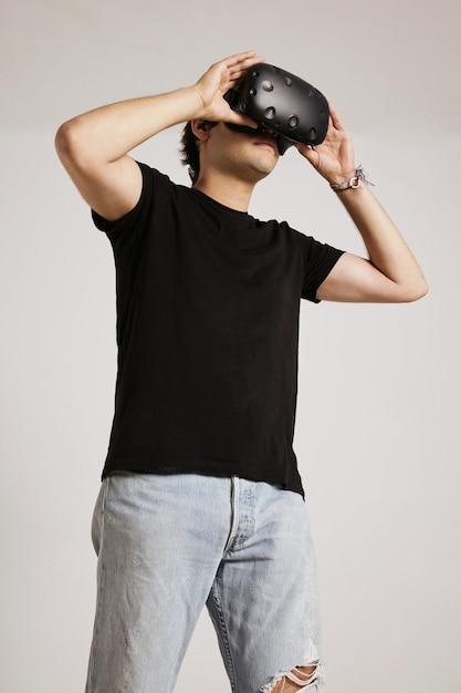 Młody Kaukaski Mężczyzna W Podartych Jasnoniebieskich Dżinsach I Czarnej Koszulce Bez Etykiety Trzyma Okulary Vr Na Twarzy Na Białym Tle Darmowe Zdjęcia