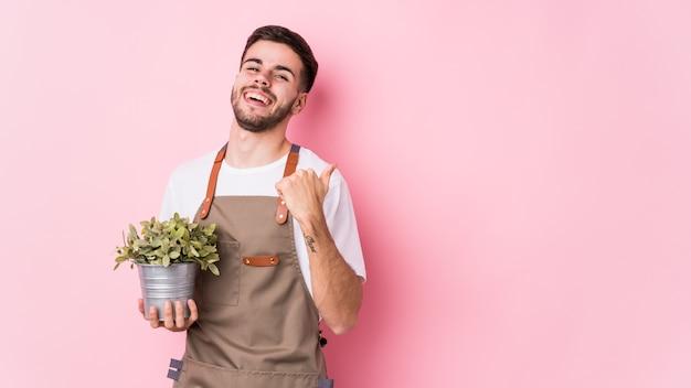 Młody Kaukaski Ogrodnik Mężczyzna Trzyma Roślinę Odizolowane Punkty Z Dala Od Kciuka, śmiejąc Się I Beztrosko. Premium Zdjęcia