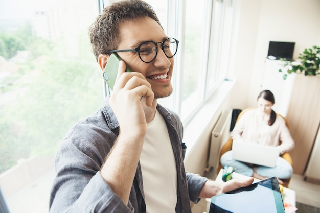 Młody Kaukaski Rodzina Biznes Pracuje W Salonie W Pobliżu Okna Na Laptopie Podczas Rozmowy Telefonicznej Premium Zdjęcia