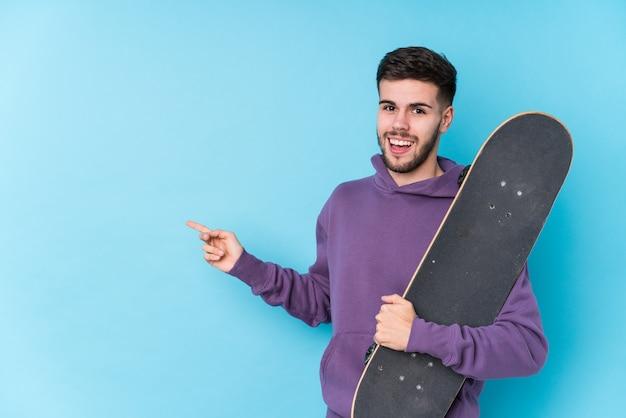Młody Kaukaski Skater Na Białym Tle, Uśmiechając Się I Wskazując Na Bok, Pokazując Coś W Pustej Przestrzeni. Premium Zdjęcia
