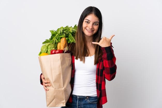 Młody Kaukaski Z Warzywami Na Białym Tle Na Białej ścianie Dzięki Telefonowi Gestowi. Oddzwoń Do Mnie Znak Premium Zdjęcia