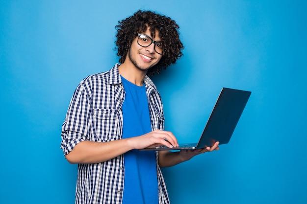 Młody Kędzierzawy Przystojny Mężczyzna Z Laptopem Odizolowywającym Na Błękit ścianie Darmowe Zdjęcia