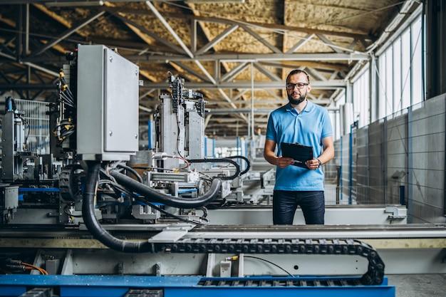 Młody Kierownik Inżyniera Z Brodą Sprawdzającą Manufakturę, Miejsce Pracy I Maszyny W Dużej Fabryce. Premium Zdjęcia