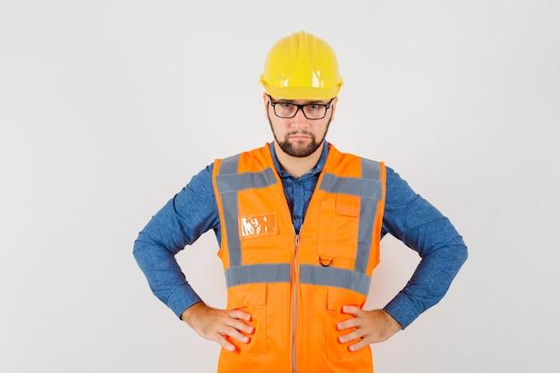 Młody Konstruktor Trzymający Się Za Ręce W Talii W Koszuli, Kamizelce, Kasku I Wyglądający Poważnie. Przedni Widok. Darmowe Zdjęcia