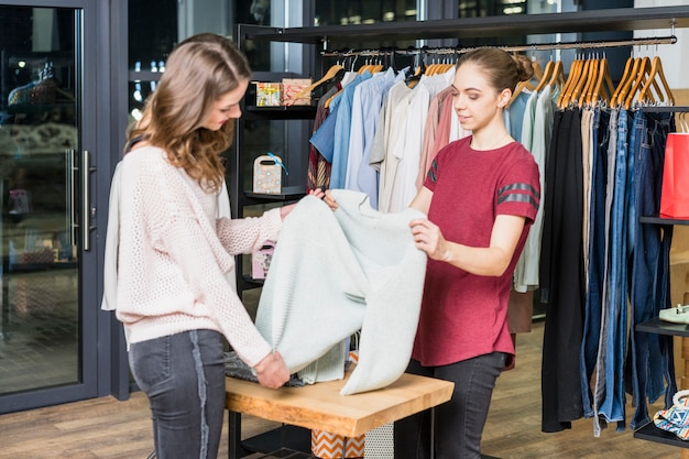 Młody konsultant pokazuje ubrania do klienta w centrum handlowym Darmowe Zdjęcia