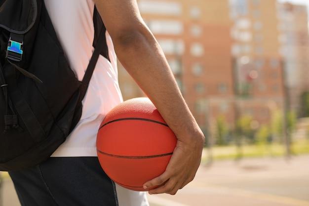 Młody Koszykarz Z Piłką I Plecakiem Stojący Na Placu Zabaw Przed Treningiem Na świeżym Powietrzu Premium Zdjęcia