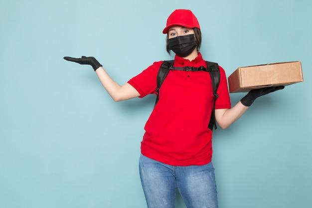 Młody Kurier W Czerwonej Koszulce Polo Czerwonej Czapce Czarna Sterylna Maska Ochronna Czarny Plecak Trzyma Pakiet Na Niebiesko Darmowe Zdjęcia