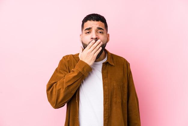 Młody łaciński Mężczyzna Na Różowej ścianie Na Białym Tle Ziewanie Pokazujący Zmęczony Gest Obejmujący Usta Ręką. Premium Zdjęcia