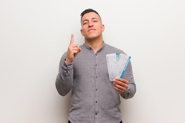 Młody łaciński mężczyzna trzyma lotniczych bilety pokazuje liczbę jeden Premium Zdjęcia