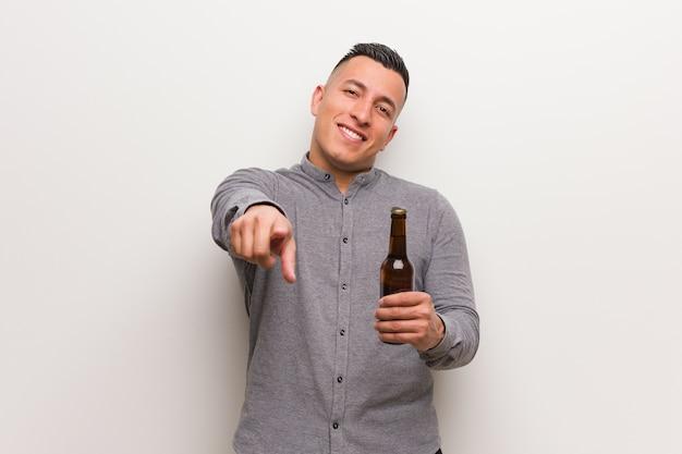 Młody łaciński Mężczyzna Trzyma Piwo Wesoła I Uśmiechnięta, Wskazując Na Przód Premium Zdjęcia