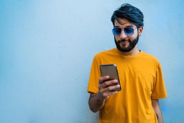 Młody łaciński Mężczyzna Używa Jego Telefon Komórkowego. Darmowe Zdjęcia
