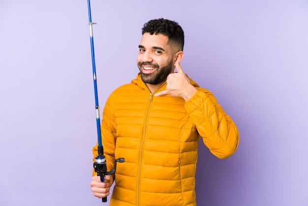 Młody łaciński Rybak Trzymający Wędkę Na Białym Tle Młody łaciński Rybak Trzymający Młodego łacińskiego Mężczyznę Grającego W Kosz Na Białym Tle Pokazujący Gest Telefonu Komórkowego Palcami Premium Zdjęcia