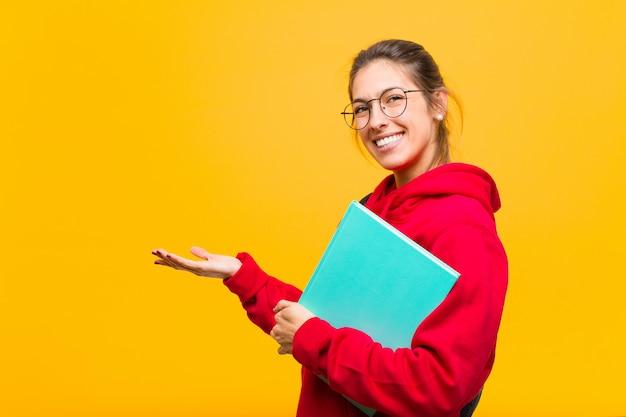 Młody ładny Studencki Ono Uśmiecha Się Radośnie, Czuje Się Szczęśliwy I Pokazuje Pojęcie W Kopii Przestrzeni Z Palmą Ręka Premium Zdjęcia