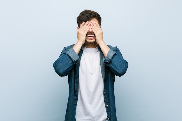 Młody latynoski fajny mężczyzna zakrywa oczy dłońmi, uśmiecha się szeroko, czekając na niespodziankę. Premium Zdjęcia