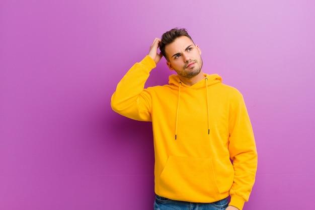 Młody latynoski mężczyzna z przypadkowym spojrzeniem przeciw purpurowemu tłu Premium Zdjęcia