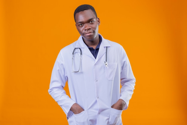 Młody Lekarz Afroamerykanin Ubrany W Biały Fartuch Ze Stetoskopem Z Rękami W Kieszeni Z Pewną Poważną Miną Darmowe Zdjęcia