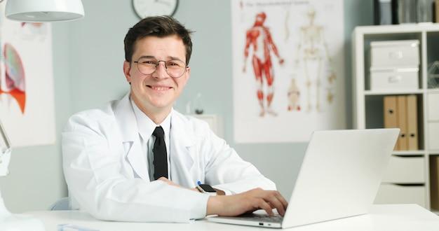 Młody Lekarz Siedzi Z Laptopem W Gabinecie Lekarskim Premium Zdjęcia